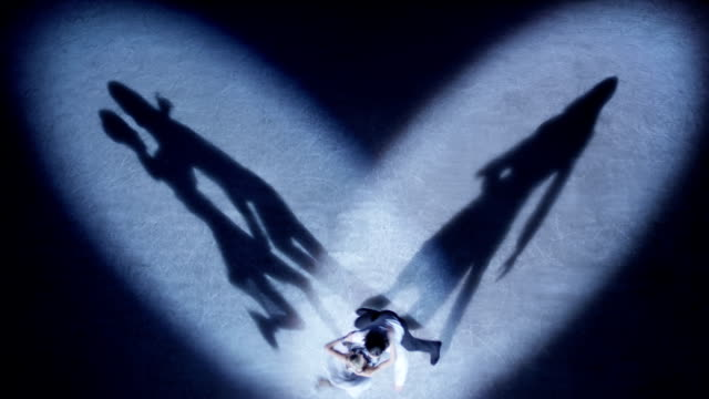 Figure skaters performing love dance in spotlight video