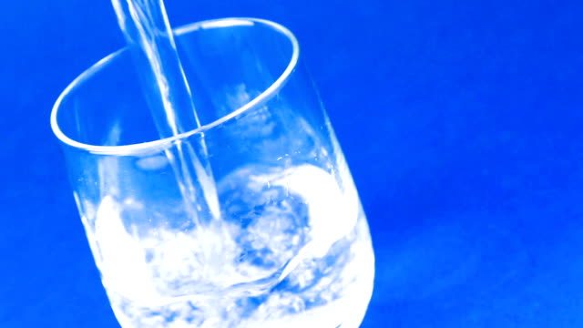 filling a glass with water on blue background, nutrition concept video
