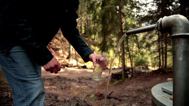 HD: Filling Bottle With Mineral Water in Forest video