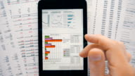 Financial analysts see charts and graphs on the screen of the touchpad video