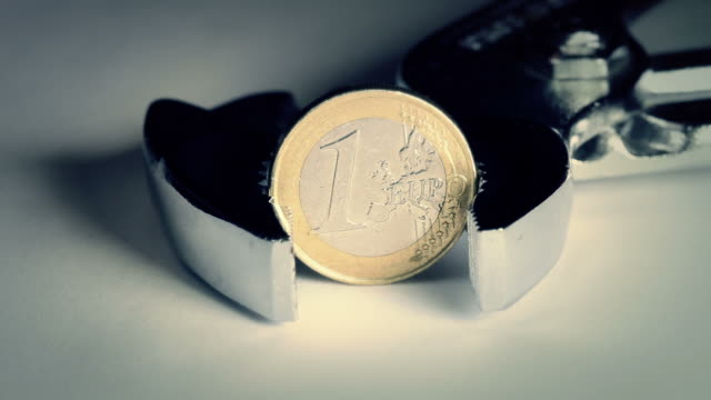 Financial Crisis and Euro: Coin Hold in a Clamp video