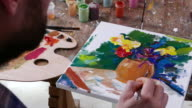 4К Fine art painter creating colorful picture with flowers in studio video