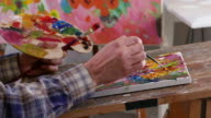 4К Fine art painter holding palette and painting in workshop video