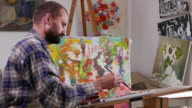 4К Fine artist holding palette and painting in his studio video