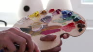 4К Fine artist holding palette and painting in workshop video