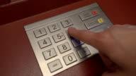 Finger entering secret pin number at ATM video