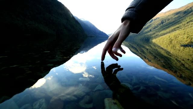 Finger touches surface of mountain lake, New Zealand video