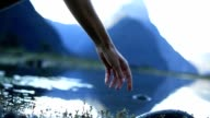 Finger touches surface of mountain lake video