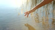 Finger touches surface of tranquil mountain lake video