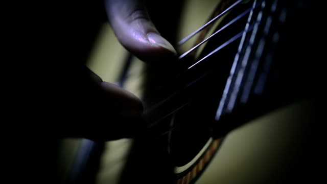 Fingers paying chords of a guitar video