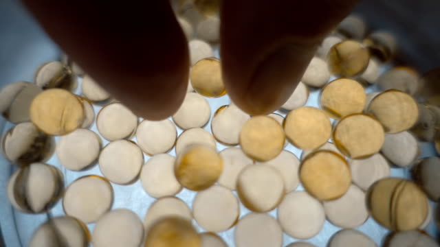 Fingers take transparent yellow medical capsules from a glass bowl video