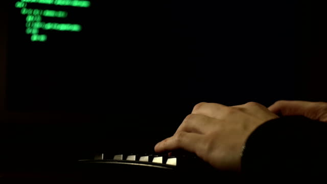 fingers typing computer code. Hacker tries to get access video