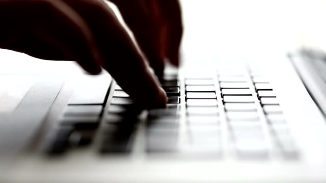 Fingers typing on a laptop video
