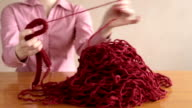 Finishing unravelling the knitting. video
