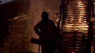 Fire fighter standing next to lit up ladder on firetruck video