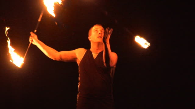Fire Juggling Spinning with Flames - Performer juggles outdoors night video
