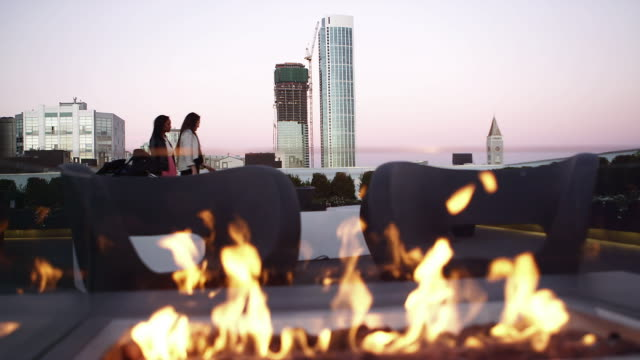 A fire pit burns on top of a roof bar as two women enter the scene from off-screen video