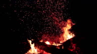 Fire sparks rising up from wood log turned over in a burning outdoor bonfire - close up video