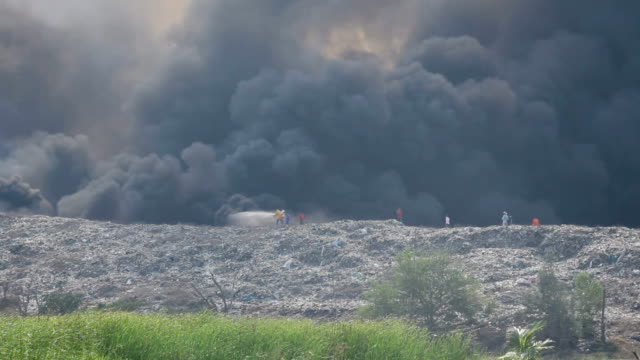 Firefighter and Burning garbage heap of smoke video