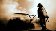 firefighter extinguish burning car. car on fire. dramatic scenery video
