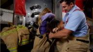 Firefighter helping little girl try on equipment video