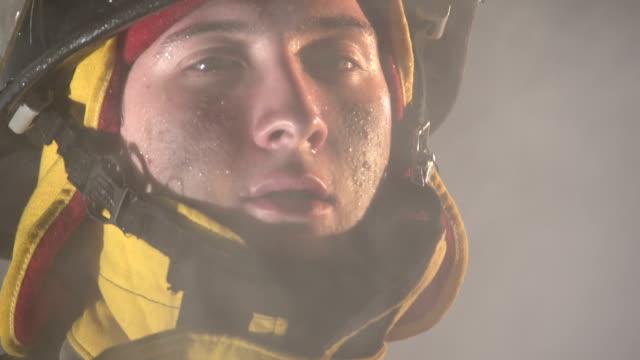 Firefighter walking towards camera through smoke, slow motion video
