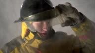 Firefighter walking towards camera through smoke, slow motion video
