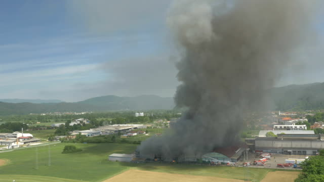 AERIAL: Firefighters extinguishing hot fire in burning agricultural factory video