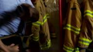 Firefighters get gear on, handheld shot video