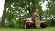 Fireman rests by leaning on his truck video