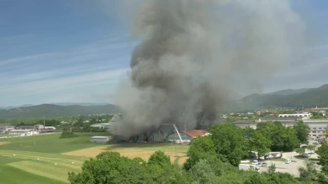 AERIAL: Firemen trying to put out the fire in burning factory in countryside video