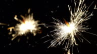 Firework sparkler burning with dancing snowflakes against black night sky background. Winter time blizzard. video