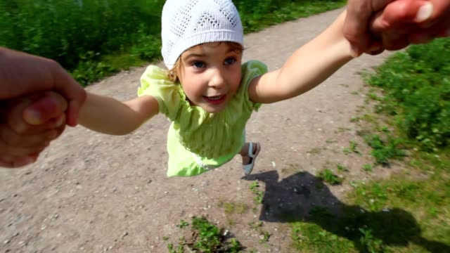 First person view from man rotates little girl in park video