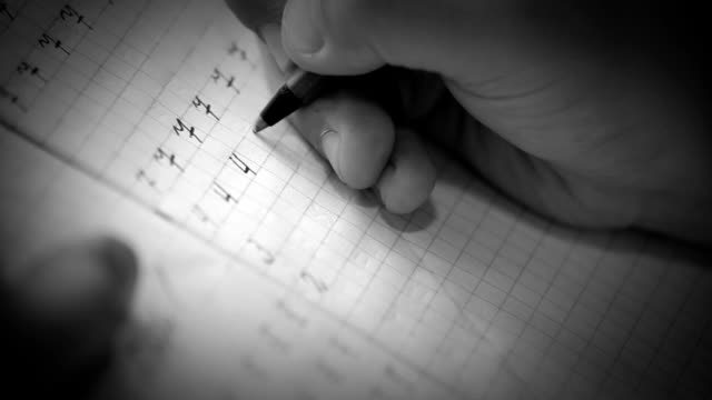 First steps in writing: little pupil write digits in square grid notebook video