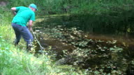 fish breeding farm worker with scythe tool clean pond from grass. video
