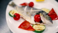 Fish decorated with cherry tomatoes. video