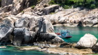 Fisher boat moving on waves at anchor between huge stone blocks in Tanote Bay, Koh Tao Island, Thailand. video