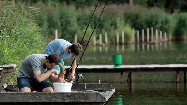 Fisherman baiting hook on fishing rod at lake video