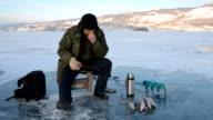 Fisherman is a man in winter fishing. video