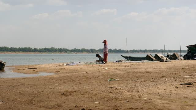 fisherman mending a fishing net by hand video