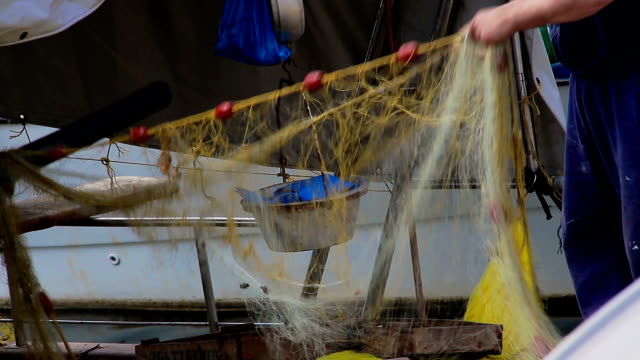 A Fisherman Mending His  Fishing Net On His Boat video
