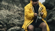 Fisherman on a rocky coast video