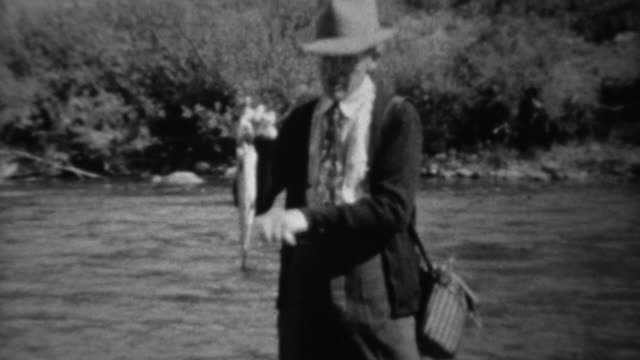 1939: Fisherman wading in fast stream showing trout fish catch. video