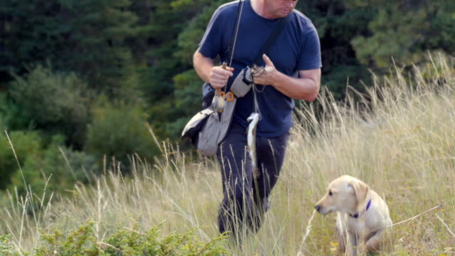 A fisherman walks through the tall grass with a fish and his dog following him video