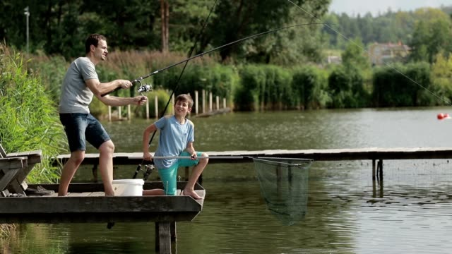 Fisherman with spinning rod catching fish on lake video