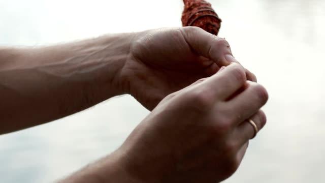 Fisherman's hands baiting fishing hook closeup video