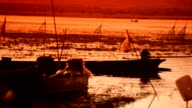 Fishermen sail out to fish at lake episode sunset video