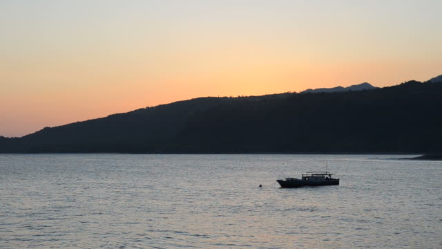 Fishing boat silhouette against sunset video
