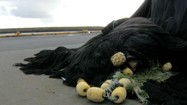 fishing nets are lying on seacoast in fishery town, static plan outdoor video