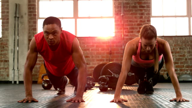 Fit couple doing push ups together in gym video